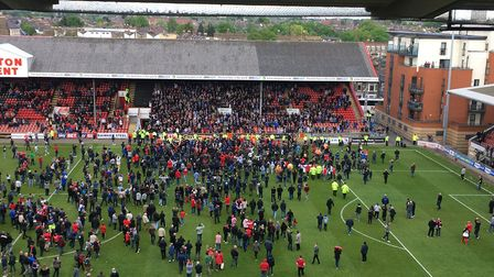 Leyton Orient fans, on the pitch, and Colchester United supporters in the far stand, applaud each ot