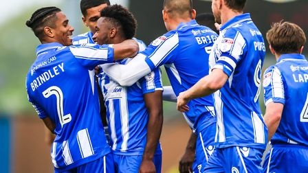 Tarique Fosu celebrates with his Colchester United team-mates after scoring his and the U's second i