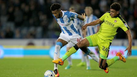 Huddersfield Town's Kasey Palmer (left) is tackled by Rotherham United's Tom Adeyemi.
