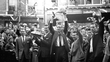 Ipswich Town skipper Andy Nelson holds the First Division Championship trophy aloft on the Cornhill