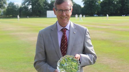 Toby Pound holds an engraved plate marking his 25 years' service as secretary of Suffolk County Cric
