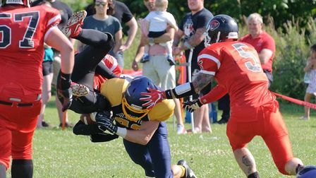 Gladiators' Adam Dickens dishes out the punishment to a Cats player for catching the ball! Photo: JO
