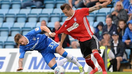 Bersant Celina has his shirt almost pulled off him by Gillingham's Mark Byrne. Picture Pagepix Ltd