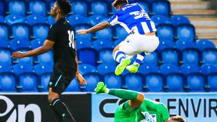 Sam Walker clutches the ball as his team-mate Lewis Kinsella leaps over him during Tuesday night's 2