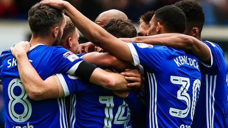 Group hug: Town players surround Martyn Waghorn after he had given them the lead in the 2-0 win over