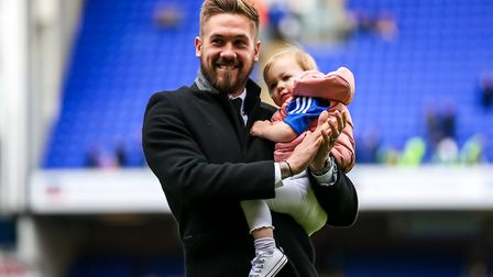 Family man: Luke Chambers pictured with one of his four children on the Portman Road pitch. Photo: S