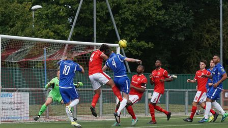 Action in the Harlow goalmouth - Rory McAuley attempts to head the ball as Dean Leacock (right) and