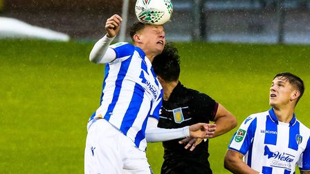 Frankie Kent wins the ball in this aerial battle during the U's Carabao Cup tie against Aston Villa.