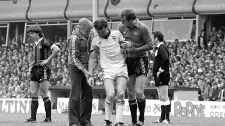 A stricken Kevin Beattie leaves the pitch for the last time as an Ipswich Town player. After battlin