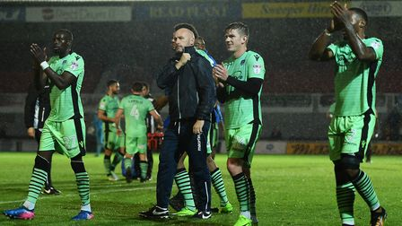 U's boss John McGreal celebrates at the final whistle with his players, in front of the away fans,