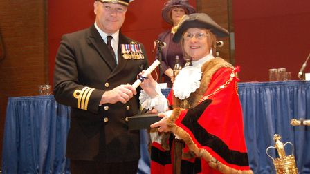 Commander Neil Lamont receives a scroll of honour from the outgoing Mayor of St Edmundsbury Cllr Jul