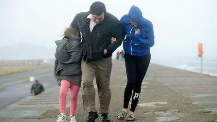 A family walking on pier wall during stormy weather. Picture: Caroline Quinn/PA Wire