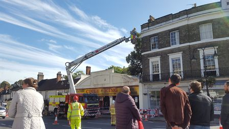 Firefighters looking at the damage at the top of the Cycle King store. Picture: MATT STOTT