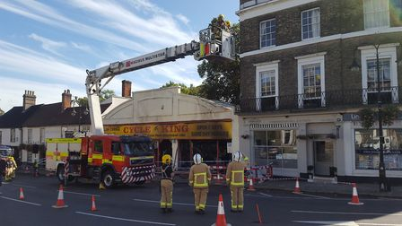 Firefighters investigating the damage caused by the fire at the Cycle King store. Picture: MATT STOT