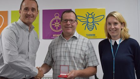 Tony Allen (centre) is presented with a medal for his 100th blood donation by chief executive of the