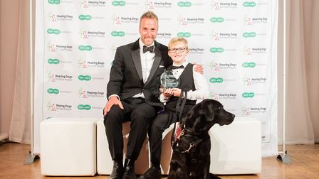 Daniel Jillings holding Varley's award at the ceremony, with Varley and Hearing Dogs Patron Ben Fogl