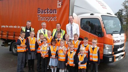 Pupils from the school alongside (left to right) Steve Moore and Charles Downie, Bacton Transport, L