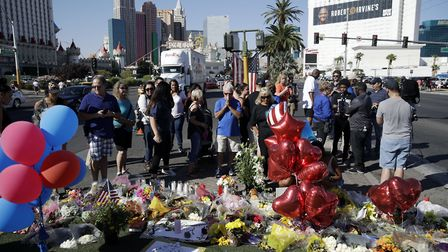 People pause at a memorial for the victims of a mass shooting in Las Vegas held on Wednesday, Octobe