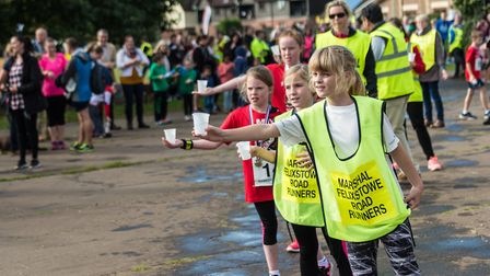 Young marshals hand out drinks to runners at the Martlesham event. Picture: PAVEL KRICKA