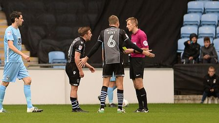 Tom Lapslie tries to argue his case before he is shown his second yellow card at the Ricoh Arena, Co