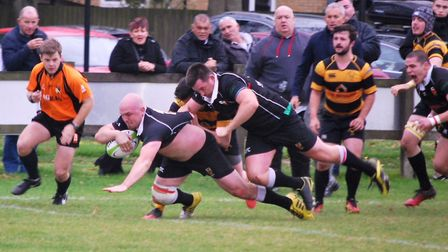 Colchester man of the match, Rhys Hartley, flies over the line, ably assisted by Eli Castle. Picture