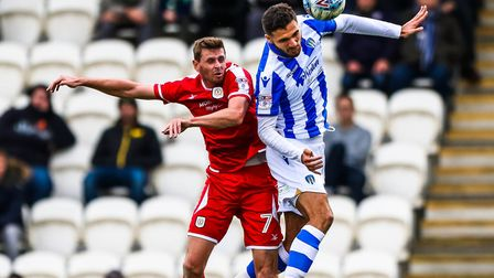 Ryan Inniss wins the ball in this aerial battle with ex-U's striker Chris Porter during last weekend