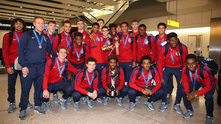 England's under 17's pose with the World Cup trophy as they arrive back to the UK, at Heathrow Airpo