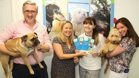 Staff at Burnett Barker Solicitors meeting some of the dogs at Bury St Edmunds Canine Creche. From l