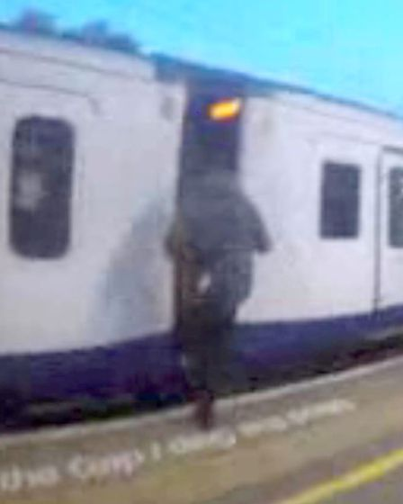 Mobile phone footage grab issued by British Transport Police of Harris Ahmed, 18, about to climb bet