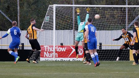 Coggeshall captain Luke Wilson (no 6) watches as his header beats James Bradbrook for the first goal