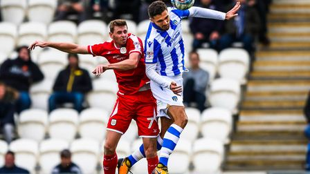 Ryan Inniss wins the ball in this battle with ex-U's striker Chris Porter. Inniss impressed again in