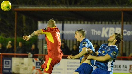 Needham Market attacker Adam Mills jumps above the Billericay defence during Tuesday night's 1-1 dra