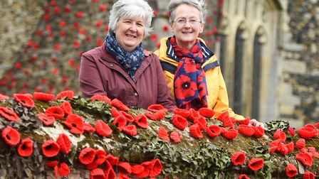 Fiona Glover and Jan Hall surrounded by 5000 poppies which have been used to yarn bomb the church i