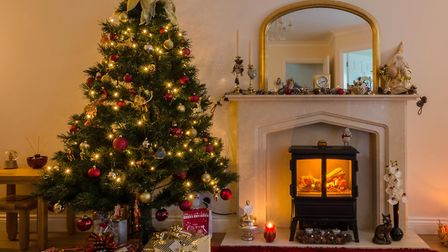 Warm glow of Christmas lights and a log burner in festive decoration