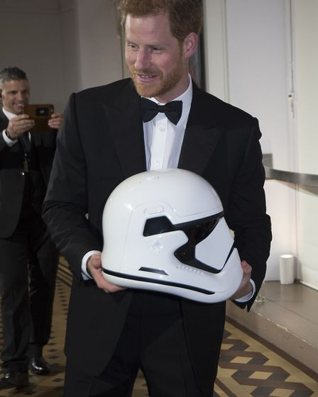 Prince Harry holds a Stormtrooper helmet as he attends the European premiere of Star Wars: The Last