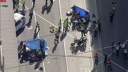 Local media say over a dozen people have been injured after a car drove into pedestrians on a sidewa