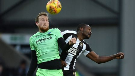 Tom Eastman, who was Carl Marston's man of the match, looks to win a header in the air against Shola