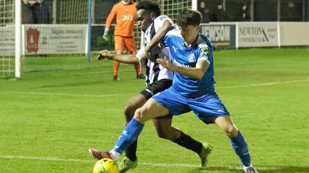 Leiston substitute Josh Cheetham battles for possession with Tooting's Tope Fadahunsi