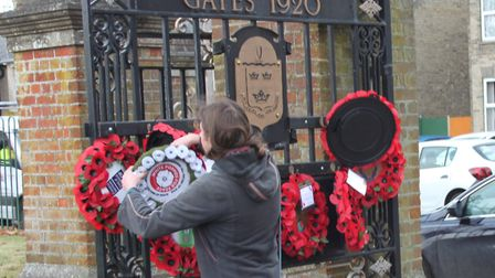 The original White Poppy wreath being put on the Memorial Gates, in Stowmarket, by councillor Miles