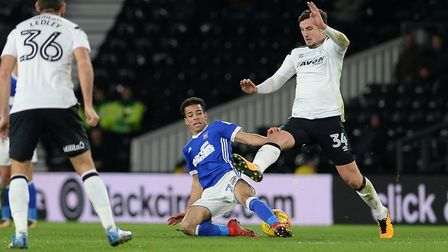 Tristan Nydam slides into a challenge on George Thorne at Derby Picture Pagepix