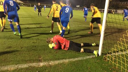 Mildenhall keeper Jacob Marsden releases the pressure for the home side with a fine save down at his