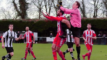 Long Melford keeper Josh Shepherd climbs above Seasider Sheridan Driver to punch away for safety. Ph