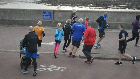 Runners negoiate a tight turn on the promenade, on an out-and-back course