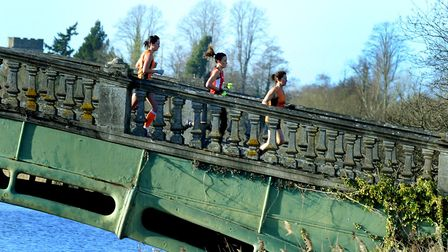 Competitors in the senior and under-20 women's race stream over the Iron Bridge during the Suffolk C