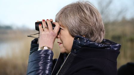 Prime Minister Theresa May looks through a pair of binoculars during a visit to the London Wetland C