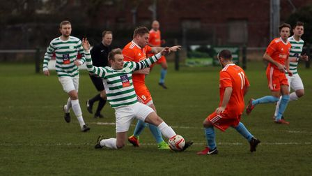 Framlingham captain James Mayhew, green and white, gets the ball from Holland's Steve Eaton in an ea