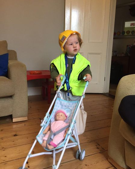 Adelaide Furniss, dressed as a builder and playing with a pram. Picture: ELLIOT FURNISS