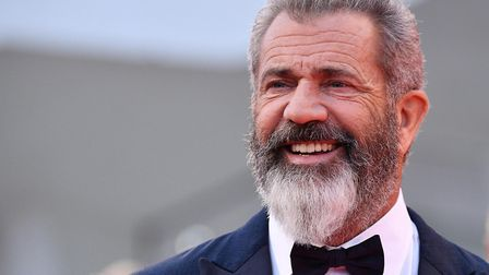 """Director and actor Mel Gibson poses as he arrives on the red carpet for """"Hacksaw Ridge"""" at the 73rd"""