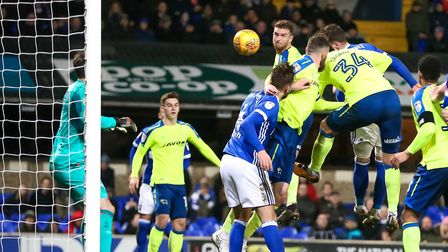 Joe Garner, partly hidden by George Thorne (34) rises high to head a goal back for Town. Picture: