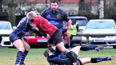 It takes three Chingford players to stop Rhys Hartley at Mill Road. Photo: RICHARD PARKER